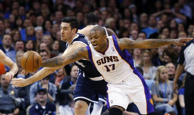 Oklahoma City Thunder forward Nick Collison, left, and Phoenix Suns forward P.J. Tucker (17) reach for the ball in the first quarter of an NBA basketball game in Oklahoma City, Monday, Dec. 31, 2012. (AP Photo/Sue Ogrocki)