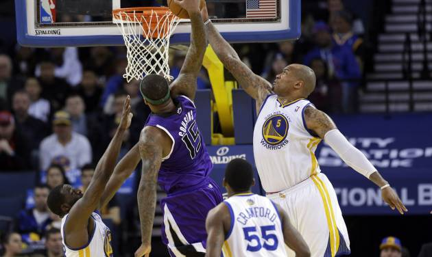 Golden State Warriors forward Marreese Speights (5) blocks a dunk attempt from Sacramento Kings center DeMarcus Cousins (15) during the second half of an NBA basketball game on Friday, April 4, 2014, in Oakland, Calif. Golden State won 102-69. (AP Photo/Marcio Jose Sanchez)