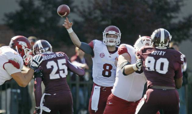 Arkansas quarterback Tyler Wilson (8) throws a pass as his teammates block Mississippi State defenders Corey Broomfield (25) and Denico Autry (90) in the first quarter of their NCAA college football game in Starkville, Miss., Saturday, Nov. 17, 2012. Mississippi State won 45-14. (AP Photo/Rogelio V. Solis)