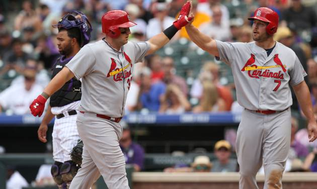 St. Louis Cardinals' Matt Adams, front left, is congratulated after hitting a two-run home run by Matt Holliday, front right, as Colorado Rockies catcher Wilin Rosario looks away in the fifth inning of a baseball game in Denver on Wednesday, June 25, 2014. (AP Photo/David Zalubowski)