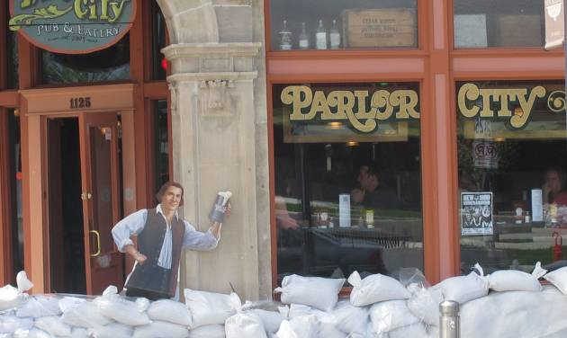 FILE - In this May 31, 2013, file photo, sandbags are piled around the Parlor City Pub and Eatery in Cedar Rapids, Iowa, where workers placed a cardboard cutout of a man drinking beer. Congress sent the White House a $12.3 billion water projects bill half the size of its last one seven years ago — before the economy sank into a deep recession that helped swell the government's debt and before lawmakers swore off cherry-picking pet projects for folks back home.  (AP Photo/Ryan J. Foley, File)