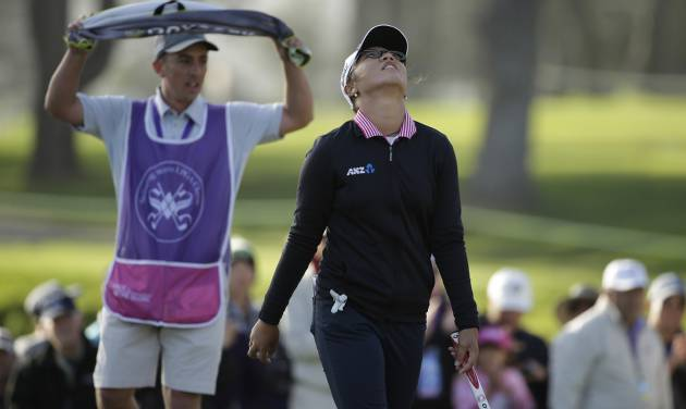 Lydia Ko of New Zealand walks off the 18th green of the Lake Merced Golf Club after winning the Swinging Skirts LPGA Classic golf tournament on Sunday, April 27, 2014, in Daly City, Calif. Ko won the event after shooting a 3-under-par 69 to finish at 12-under-par. At left is her caddie Domingo Jojola. (AP Photo/Eric Risberg)