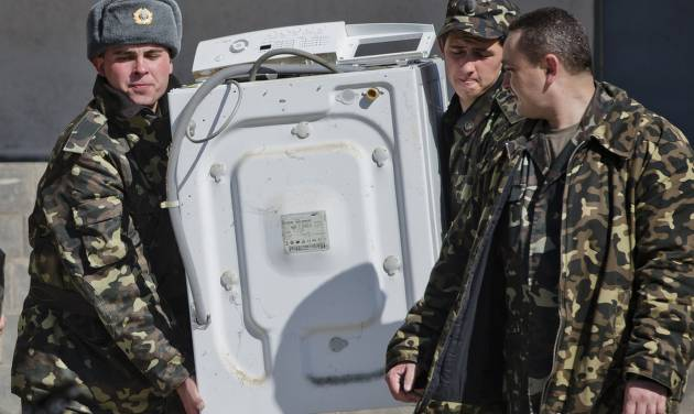 Ukrainian airmen carry a washing machine while removing their belongings from the Belbek air base, outside Sevastopol, Crimea, Friday, March 21, 2014. The base commander Col. Yuliy Mamchur said he was asked by the Russian military to turn over the base but is unwilling to do so until he receives orders from the Ukrainian defense ministry. (AP Photo/Vadim Ghirda)