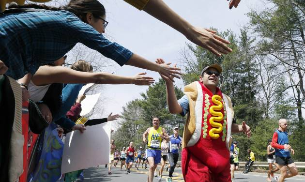 FILE -- In this April 15, 2013 file photo, a man dressed as a hot dog runs through Wellesley, Mass., during the 117th running of the Boston Marathon. Security will be tightened for the 2014 Boston Marathon after twin explosions killed three people and injured more than 260 near the finish line of the race in 2013. New rules include a limit on the size of water bottles, restrictions on bulky costumes, and nothing covering the face.(AP Photo/Michael Dwyer, File)
