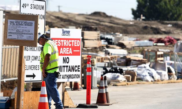A security guard walks by a construction entrance at the Forty-Niners' new stadium Monday, Oct. 14, 2013, in Santa Clara, Calif., where a second worker has been killed in an accident in less than four months.  A delivery truck driver was crushed early Monday by a bundle of rebar being unloaded from his truck, officials at the scene said. (AP Photo/Mathew Sumner)