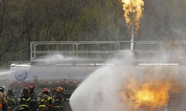 Firefighters spray fire suppressant foam to douse flames on a tanker truck in a simulated oil spill fire during a drill on Wednesday, May 7, 2014, in Albany, N.Y. Firefighters are getting some practice battling crude oil fires as part of stepped-up efforts by the Cuomo administration to address safety threats from increased rail shipment of highly flammable crude from North Dakota to East Coast refineries. The Port of Albany has become a major hub for crude oil transport, with oil trains arriving daily on routes that cross the state from the west and north. (AP Photo/Mike Groll)