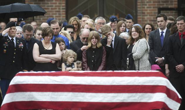 In this May 2, 2014 photo, family, friends and members of the military gather beside Kryn Miner's casket after his funeral outside St. Lawrence Church in Essex, Vt. His widow Amy Miner, third from left, believes the Veterans Affairs health system must do more to help veterans who struggle with Post Traumatic Stress Disorder after returning home. (AP photo/Burlington Free Press, Emily McManamy)