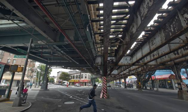 """A young man runs under an elevated section of subway tracks in The Bronx borough of New York,  Wednesday, May 22, 2013.  A company that offered tourist treks to the Bronx """"ghetto"""" has shut down under scathing criticism from neighborhood leaders offended by the tours that took mostly European and Australian tourists past food-pantry lines and """"pickpocket"""" park. But other New York companies continue to show visitors,  many of them foreigners who know of the Bronx only from movies, the grittiest part of the city's poorest borough. (AP Photo/Richard Drew)"""