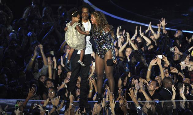 Beyonce on stage hugs Jay Z and their daughter Blue Ivy as she accepts the Video Vanguard Award at the MTV Video Music Awards at The Forum on Sunday, Aug. 24, 2014, in Inglewood, Calif. (Photo by Chris Pizzello/Invision/AP)