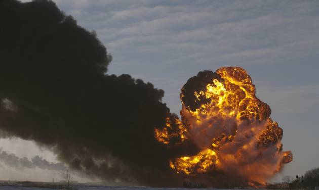 """FILE - In this Dec. 30, 2013 file photo, a fireball goes up at the site of an oil train derailment in Casselton, N.D. Former North Dakota governor and Casselton native George Sinner wants new regulations placed upon railroads that transport crude oil from the state. Sinner says the derailment of tanker cars and ensuing fire outside Casselton shows what he calls a """"ridiculous threat"""" to communities across the United States. (AP Photo/Bruce Crummy, File)"""