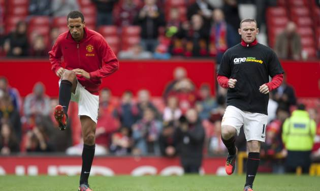 Manchester United's Rio Ferdinand, left, is seen without an anti-racism shirt alongside teammate Wayne Rooney as the team warms up before their English Premier League soccer match against Stoke at Old Trafford Stadium, Manchester, England, Saturday, Oct. 20, 2012. (AP Photo/Jon Super)