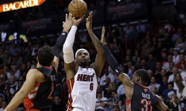 Miami Heat forward LeBron James (6) shoots against Toronto Raptors forward Landry Fields (2) and guard Terrence Ross (31) during the first half of an NBA basketball game on Wednesday, Jan. 23, 2013, in Miami. (AP Photo/Wilfredo Lee)