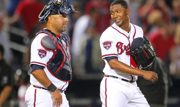 Atlanta Braves starting pitcher Julio Teheran talks with catcher Gerald Laird at the end of a baseball game against the Milwaukee Brewers Tuesday, May 20, 2014, in Atlanta. Teheran pitched a complete game as the Braves won 5-0. (AP Photo/Todd Kirkland)