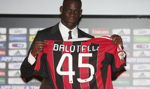 Italian striker Mario Balotelli poses with his new AC Milan jersey during an official presentation at the San Siro stadium in Milan, Italy, Friday, Feb. 1, 2013. Balotelli is expected to make his official debut for the Rossoneri against Udinese after his move from Manchester City. Balotelli finalised a €20 million transfer returning to Italy after a turbulent 2 1/2 years in the Premier League. (AP photo/Antonio Calanni) (AP Photo/Antonio Calanni)
