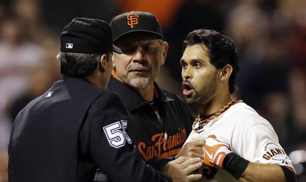 San Francisco Giants' Angel Pagan, right, is held back by manager Bruce Bochy, center, as he argues with home plate umpire Angel Hernandez after a strike out during the sixth inning of a baseball game against the Colorado Rockies on Tuesday, Sept. 18, 2012 in San Francisco. (AP Photo/Marcio Jose Sanchez)