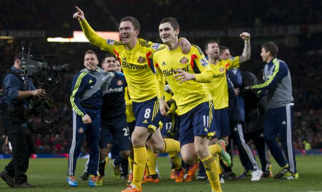 Sunderland's Craig Gardner, centre left, celebrates with teammate Adam Johnson after their team's penalty win against Manchester United during their English League Cup semifinal second leg soccer match at Old Trafford Stadium, Manchester, England, Wednesday Jan. 22, 2014. (AP Photo/Jon Super)