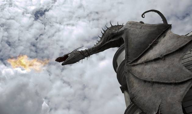 A dragon breathes fire from atop Gringnotts Bank during a preview of Diagon Alley at the Wizarding World of Harry Potter at Universal Orlando, Thursday, June 19, 2014, in Orlando, Fla. (AP Photo/John Raoux)