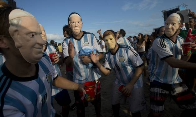 """FILE - In this Wednesday, July 9, 2014 file photo, soccer fans of the Argentina national soccer team wear masks with faces of Pope Francis and Argentine soccer player Lionel Messi during a live telecast of the soccer World Cup semifinal match between Argentina and Netherlands, inside the FIFA Fan Fest area on Copacabana beach, in Rio de Janeiro, Brazil. The Vatican says it is unlikely that Pope Francis and his predecessor, Pope Emeritus Benedict XVI, would get together to watch their home teams in the World Cup final on Sunday. Vatican spokesman, the Rev. Federico Lombardi, said Thursday, July 10, 2014 that the hour of the final is late for Francis' routine, and acknowledged with a chuckle that Benedict wasn't known as an avid sports fan. Still, he didn't rule anything out, saying, """"we'll see in the coming days."""" Pope Francis has already given his word that there would be no papal intervention in Argentina's fortunes, promising he wouldn't pray for any team. German-born Benedict's interests are known to lean more toward intellectual than athletic pursuits. (AP Photo/Silvia Izquierdo, File)"""
