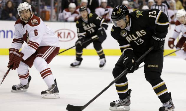Dallas Stars' Ray Whitney (13) prepares to take a shot on-goal under pressure fro Phoenix Coyotes' David Schlemko (6) in the first period of an NHL hockey game on Friday, Feb. 1, 2013, in Dallas. (AP Photo/Tony Gutierrez)