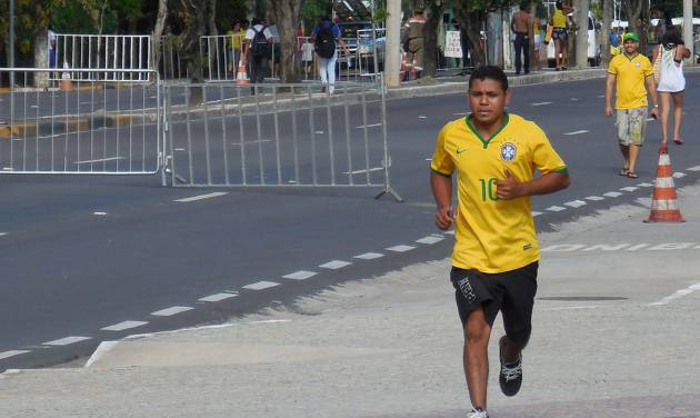 A man wearing a No. 10 Brazil soccer jersey jogs along the Rio Negro in Manaus, Brazil, Monday, June 23, 2014. There are about a dozen running groups in Manaus, in spite of the heat and humidity. (AP Photo/Chris Lehourites)