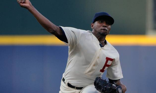 Wearing a 1914 throwback uniform to commemorate the World Series-winning Boston Braves, Atlanta Braves starting pitcher Julio Teheran delivers to the Oakland Athletics during the first inning of a baseball game Saturday, Aug. 16, 2014, in Atlanta. (AP Photo/David Tulis)