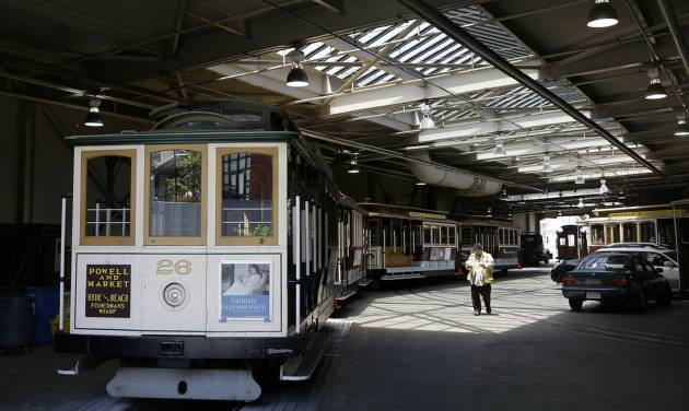 A worker walks past cable cars not in service at the cable car barn and powerhouse in San Francisco, Tuesday, June 3, 2014. San Francisco's famed cable cars were halted for a second straight day, and the rest of the city's transit system experienced delays after drivers called in sick again on Tuesday, days after overwhelmingly rejecting a new labor contract, officials said. (AP Photo/Jeff Chiu)