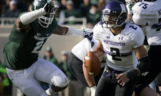 Northwestern quarterback Kain Colter, right, scrambles against Michigan State's William Gholston during the first quarter of an NCAA college football game, Saturday, Nov. 17, 2012, in East Lansing, Mich. (AP Photo/Al Goldis)