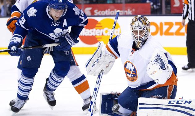 Toronto Maple Leafs forward Joffrey Lupul, left, battles for the lose puck against New York Islanders goalie Kevin Poulin, right, during second period of an NHL hockey game in Toronto, Tuesday, Jan. 7, 2014. (AP Photo/The Canadian Press, Nathan Denette)