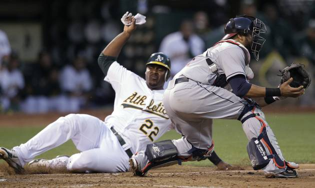 Oakland Athletics' Chris Carter, left, slides to score past Cleveland Indians catcher Carlos Santana in the sixth inning of a baseball game Saturday, Aug. 18, 2012, in Oakland, Calif. Carter scored on a single by George Kottaras. (AP Photo/Ben Margot)
