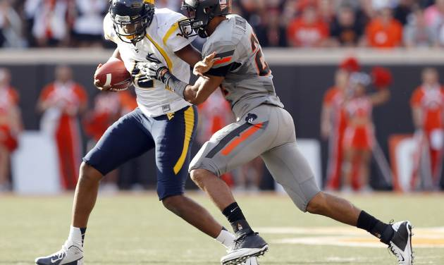 Oklahoma State's Lyndell Johnson (27) tackles West Virginia's Geno Smith (12) as he scrambles during a college football game between Oklahoma State University (OSU) and the West Virginia University at Boone Pickens Stadium in Stillwater, Okla., Saturday, Nov. 10, 2012. OSU won 55-34. Photo by Sarah Phipps, The Oklahoman  SARAH PHIPPS