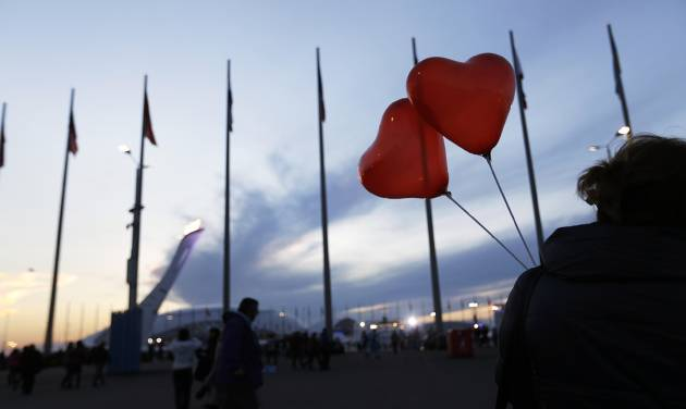 The Olympic flame burns in the background as a visitor walks through the Olympic Park with heart shaped balloons in celebration of Valentine's Day at the 2014 Winter Olympics, Friday, Feb. 14, 2014, in Sochi, Russia. (AP Photo/David Goldman)