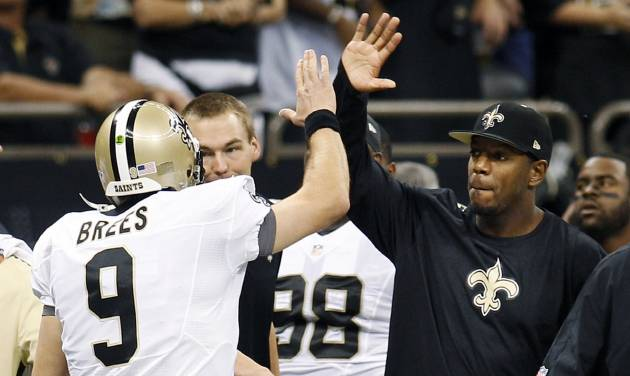 New Orleans Saints linebacker Jonathan Vilma, right, greets quarterback Drew Brees (9) after Brees' touchdown pass in the first half of an NFL football game against the Washington Redskins in New Orleans, Sunday, Sept. 9, 2012. (AP Photo/Bill Haber)