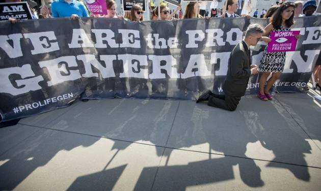 Michael Hichborn kneels and prays as he joins demonstrators while waiting for the Supreme Court's decision on the Hobby Lobby case outside the Supreme Court in Washington, Monday, June 30, 2014. The Supreme Court says corporations can hold religious objections that allow them to opt out of the new health law requirement that they cover contraceptives for women.(AP Photo/Pablo Martinez Monsivais)