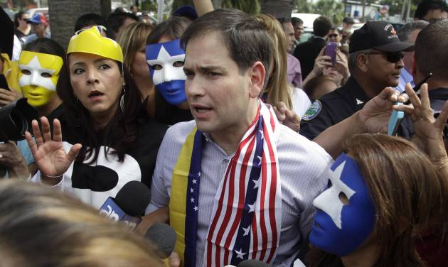 FILE - In this Feb. 28, 2014 file photo, surrounded by mask-wearing supporters of Venezuela's opposition, U.S. Senator Marco Rubio, center, speaks to the media in Doral, Fla. Rubio and Gov. Rick Scott called for sanctions against Venezuela, as opponents of President Nicolas Maduro were staging countrywide protests. Amid escalating tensions with Venezuela, the U.S. State Department on Wednesday, July 30, 2014, announced sanctions against Venezuelan officials it said committed human rights abuses during the spring crackdown on anti-government protests.  (AP Photo/Javier Galeano, File)