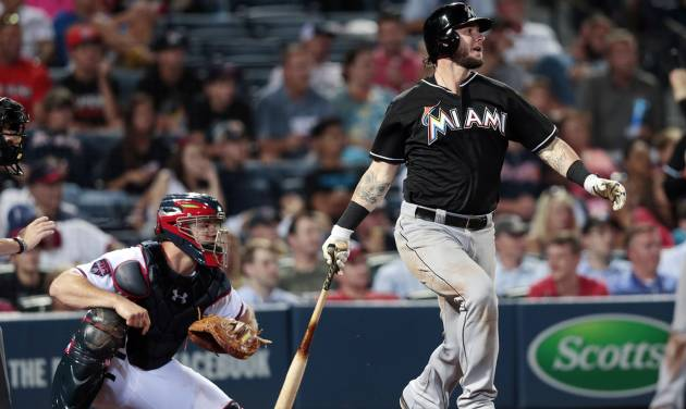 Miami Marlins' Jarrod Saltalamacchia, right, drives in the game-wining run with a base hit as Atlanta Braves catcher Evan Gattis looks on in the ninth inning of a baseball game on Thursday, July 24, 2014, in Atlanta. The Marlins won 3-2. (AP Photo)