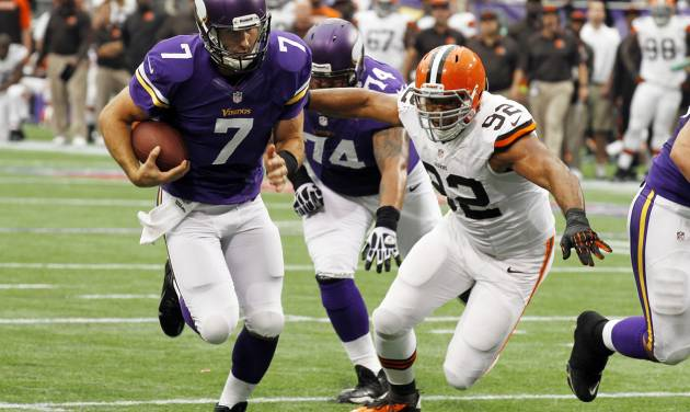 FILE - In this Sept. 22, 2013, file photo, Minnesota Vikings quarterback Christian Ponder, left, runs from Cleveland Browns defensive end Desmond Bryant while scoring on a 6-yard touchdown run in the first half of an NFL football game in Minneapolis. Browns defensive lineman Bryant says he's completely healthy and relieved to be playing again after having a heart operation. Bryant underwent a cardiac ablation on Dec. 6, a procedure to correct an irregular heartbeat he had suffered with for years. (AP Photo/Ann Heisenfelt, File)