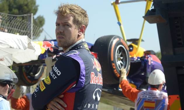Red Bull driver Sebastian Vettel of Germany looks around as his car is taken away after he lost control  during a first free practice session at the Barcelona Catalunya racetrack in Montmelo, near Barcelona, Spain, Friday, May 9, 2014. The Formula One race will be held on Sunday. (AP Photo/Manu Fernandez)