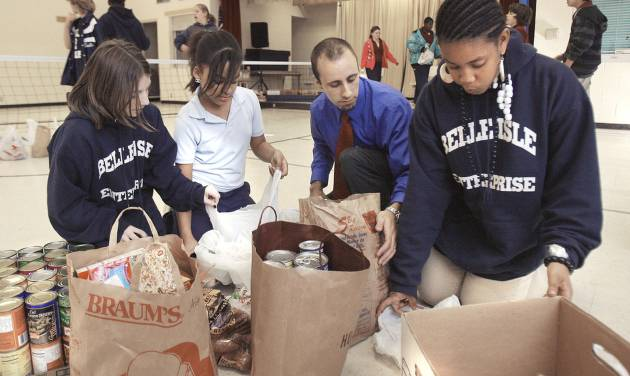 Belle Isle Enterprise Middle School students Bethany Goodman, 11, Mikayla Nevills, 12, science teacher Dan Covey and Kori Long, 11, sort food donations to assist families in need this Thanksgiving.