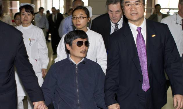 FILE - In this file photo taken Wednesday, May 2, 2012. and released by the U.S. Embassy Beijing Press Office, blind lawyer Chen Guangcheng, center, holds hands with U.S. Ambassador to China, Gary Locke, at a hospital in Beijing. Locke wasn't considered much of a heavyweight on human rights when he became the first Chinese-American ambassador to Beijing last year. Yet, nine months on, Locke's key role in the recent drama over Chen has put him on the front lines of U.S. concerns about China's embattled dissident community. (AP Photo/U.S. Embassy Beijing Press Office, File)