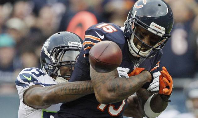 Chicago Bears wide receiver Brandon Marshall (15) fumbles after getting hit by Seattle Seahawks cornerback Brandon Browner (39) in the first half of an NFL football game in Chicago, Sunday, Dec. 2, 2012. Marshall recovered his own fumble.  (AP Photo/Nam Y. Huh)