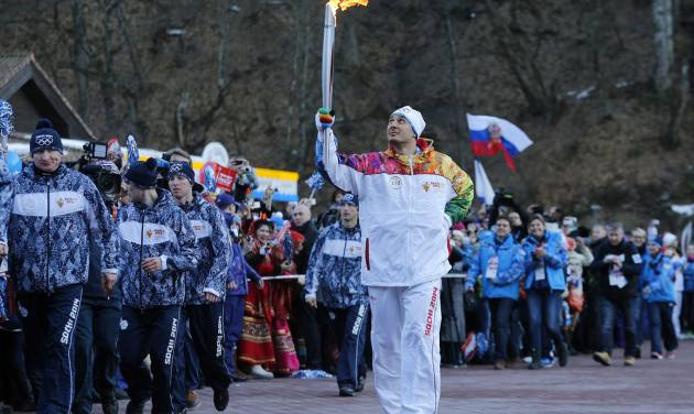 Alexey Voyevoda, a former Olympic bobsledder, who won silver in the 4-man bobsled in Turin in 2006, carries the Olympic torch as it makes it's way throughout the streets of the Rosa Khutor ski resort in Krasnaya Polyana, Russia at the Sochi 2014 Winter Olympics, Wednesday, Feb. 5, 2014.  (AP Photo/Christophe Ena)