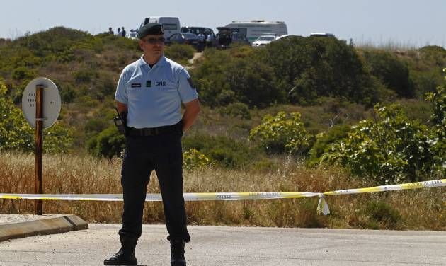 A Portuguese Republican Guard policeman stands guard by a cordoned-off area with other officers, background, in Praia da Luz, Lagos, southern Portugal, Monday, June 2, 2014. Police investigating the disappearance of Madeleine McCann cordoned off Monday an area of scrubland near where the British girl vanished seven years ago. Officers placed yellow-and-white police tape around the waste ground, which is mostly level and slightly larger than a soccer field, and were expected to conduct a forensic examination of the area in the coming days. (AP Photo/Francisco Seco)