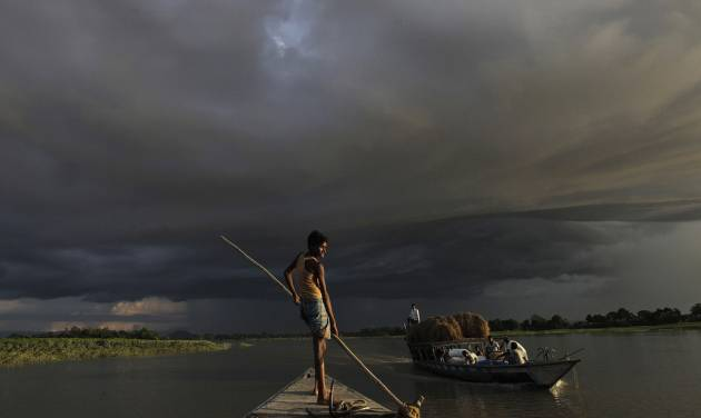 A boat carries flood relief materials as monsoon clouds surrounded the flood affected Gagalmari village in Assam state, India, Monday, July 2, 2012. The floods from monsoon rains in northeastern India killed dozens of people, with more than 2,000 villages inundated as rivers breached their banks, an official said Sunday. (AP Photo/Anupam Nath)