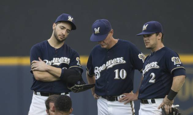 Carlos Gomez of the Milwaukee Brewers is treated by a member of the training staff after colliding with Ryan Braun in the outfield against the Colorado Rockies during the seventh inning of a baseball game Saturday, June 28, 2014, in Milwaukee. Looking on are teammates Ryan Braun, Scooter Gennett and manager Ron Roenicke.  (AP Photo/Tom Lynn)