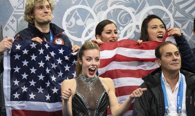 Ashley Wagner from the United States, surrounded by teammates reacts to her marks after competing in the women's team short program figure skating competition at the Iceberg Skating Palace during the 2014 Winter Olympics, Saturday, Feb. 8, 2014, in Sochi, Russia.  (AP Photo/The Canadian Press, Paul Chiasson)