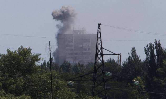 Smoke from shelling rises over a residential apartment house in Shakhtarsk, Donetsk region, eastern Ukraine on Monday, July 28, 2014. An international police team abandoned its attempt to reach the crash site of a Malaysia Airlines plane for a second day running Monday as clashes raged in a town on the road to the area.(AP Photo/Dmitry Lovetsky)