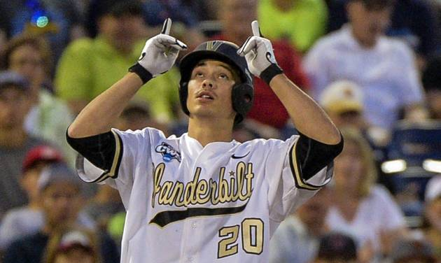 Vanderbilt's Bryan Reynolds (20) gestures at third base after hitting a triple that scored Dansby Swanson in the fourth inning of an NCAA baseball College World Series game in Omaha, Neb., Saturday, June 14, 2014. (AP Photo/Ted Kirk)