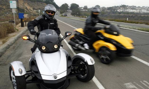 In this Feb. 9 2007 file photo provided by Can-Am Spyder, test riders pull out onto the highway for a test ride at the unveiling of the 2008 Can-Am Spyder roadster in Del Mar, Calif. U.S. safety regulators are investigating two reports of fires in Can-Am Spyder three-wheeled motorcycles. The probe announced Friday, Aug. 8, 2014 covers about 52,000 motorcycles from the 2008 through 2014 model year. (AP Photo/Can-Am Spyder, Denis Poroy, File)