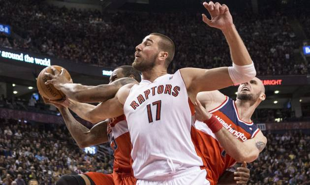 Toronto Raptors' Jonas Valanciunas, center, battles for a rebound with Washington Wizards' Trevor Booker, left, and Marcin Gortat during first half NBA basketball action in Toronto, Thursday, Feb. 27, 2014. (AP Photo/The Canadian Press, Chris Young)