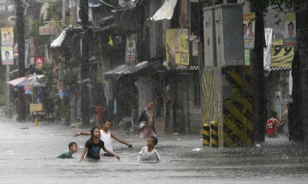 Children play in floodwaters following heavy monsoon rains spawned by a tropical depression in Manila, Philippines, Saturday July 21, 2012. The heavy rains flooded most parts of metropolitan Manila Saturday forcing cancellation of classes, creating massive traffic jams and closure of some businesses. (AP Photo/Bullit Marquez)